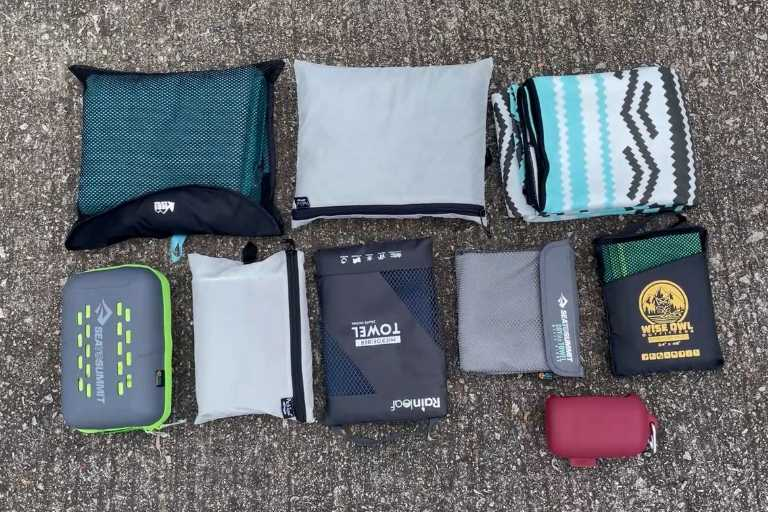 Here's what the storage pouches of 9 of the best camping towels look like. I'm missing the REI Lite's storage pouch from this shot because I forgot about it (oops). Top row from the left: REI Multi, PackTowl Luxe, Nomadix (Nomadix does not come with a storage pouch). Second row from the left: Sea to Summit Tek towel, PackTowl Personal, Rainleaf towel, Sea to Summit DryLite towel, Wise Owl Towel. The last red storage pouch belongs to the Matador NanoDry.