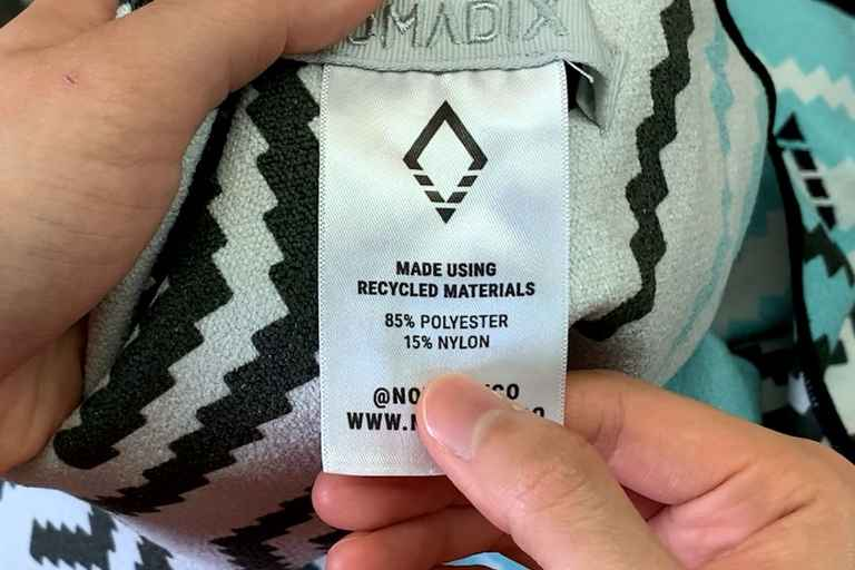 The Nomadix Original Towel product tag showing that it's made of 85% polyester and 15% nylon.