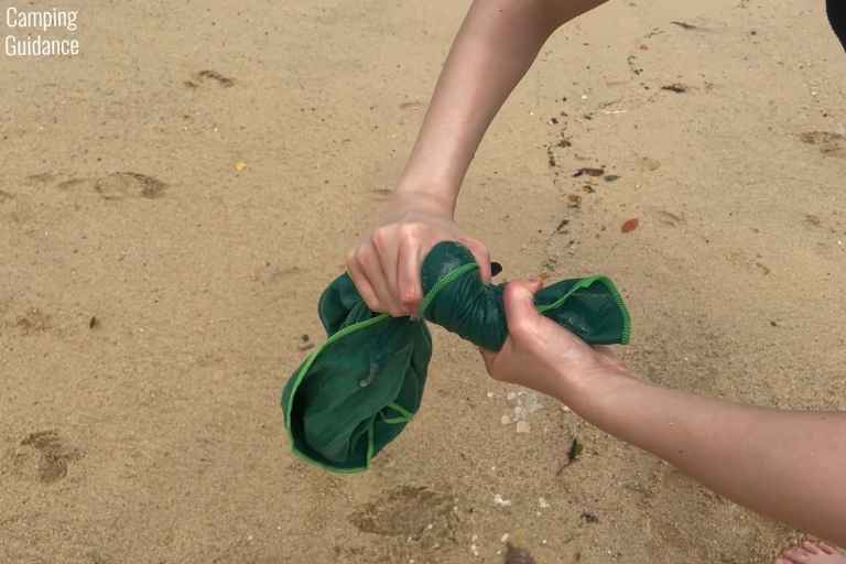 Wringing out excess seawater from the Wise Owl Towel after soaking it in seawater at a beach.