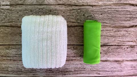 Rolled up Sea to Summit Pocket Towel (right) beside a similar sized cotton towel (left).